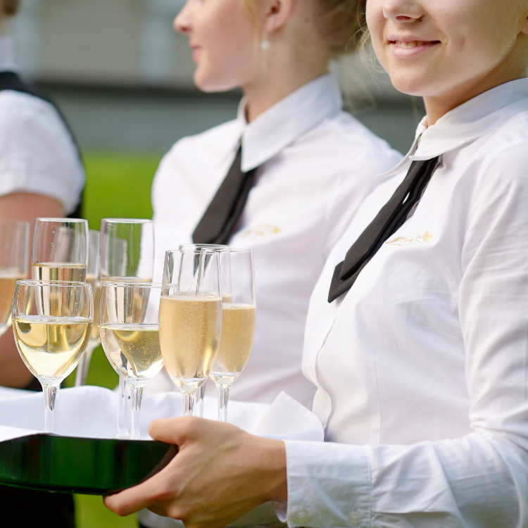 A waiter holding a tray of champagne