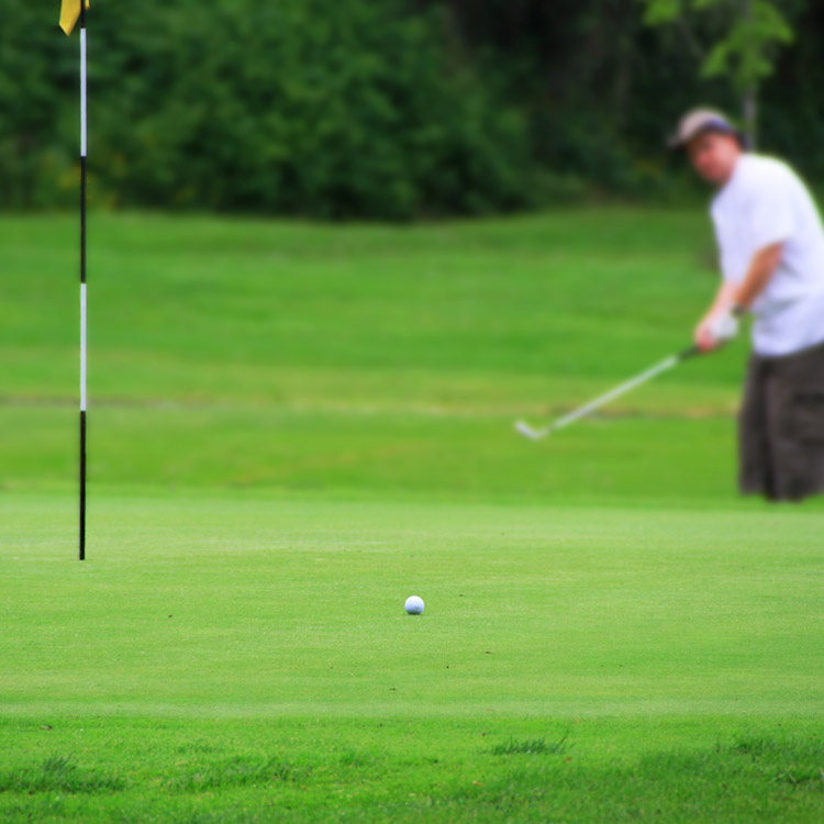 A blurred man putting on a golf courses green